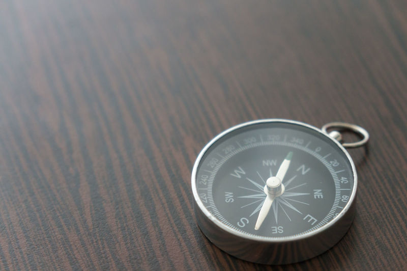 High Angle View Of Navigational Compass On Table
