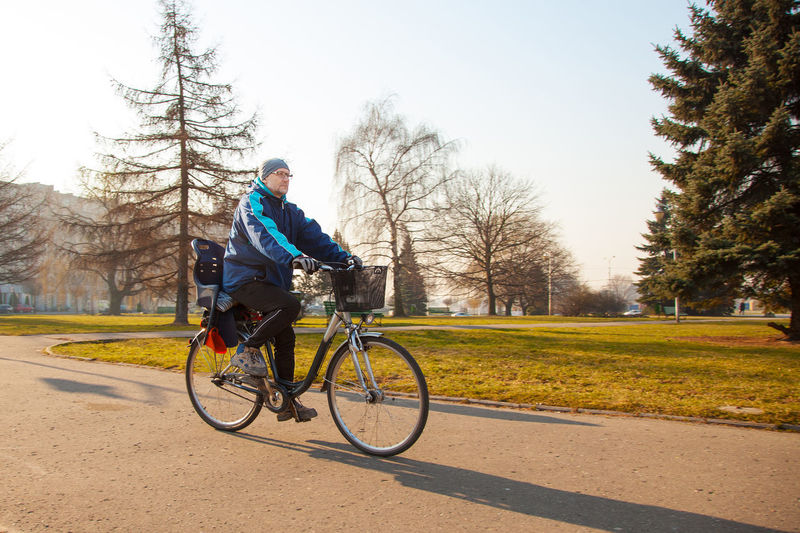 Man riding bicycle on road at park