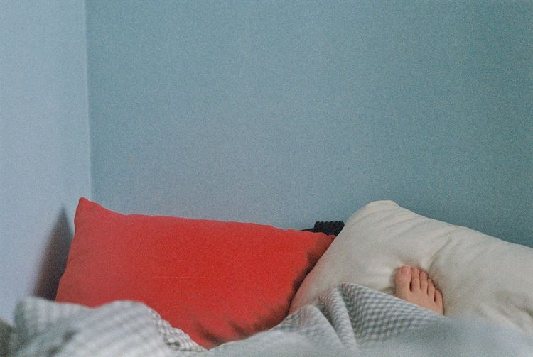 Low section of person relaxing on bed against wall