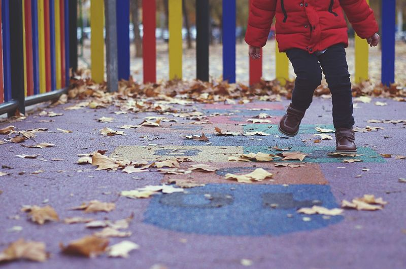 Low section of child playing hopscotch at playground during autumn
