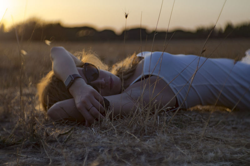 Young Woman Lying On Grassy Field During Sunset