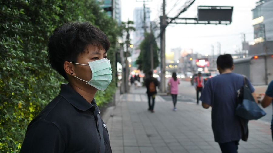 Man wearing pollution mask standing on sidewalk in city