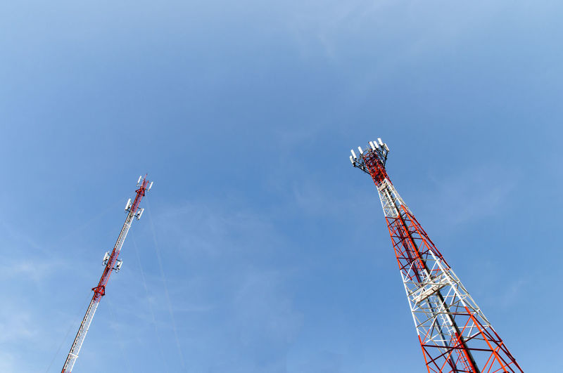 Low angle view of communication towers against blue sky