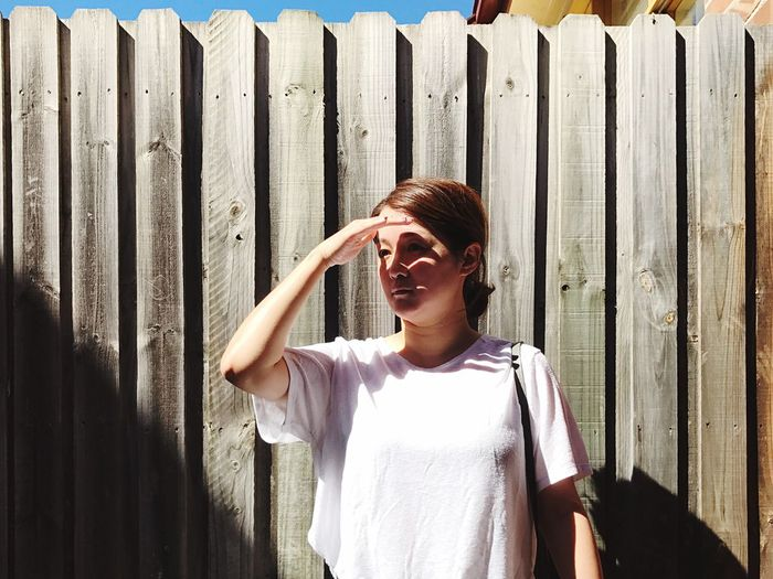 Woman Looking Away While Shielding Eyed Against Wooden Fence