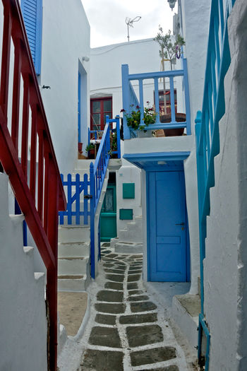 street view of Chora in Mykonos with colored external buildings Architecture Building Exterior Built Structure Building Staircase House No People Day Steps And Staircases Residential District Nature Entrance Absence Outdoors Door Blue Empty The Way Forward Direction Alley Mykonos,Greece Greek Greek Architecture Street View Urban Cityscape Colored Buildings Tourism Destination Highlights