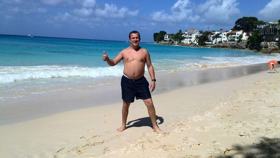 Shirtless man gesturing thumbs up sign at beach