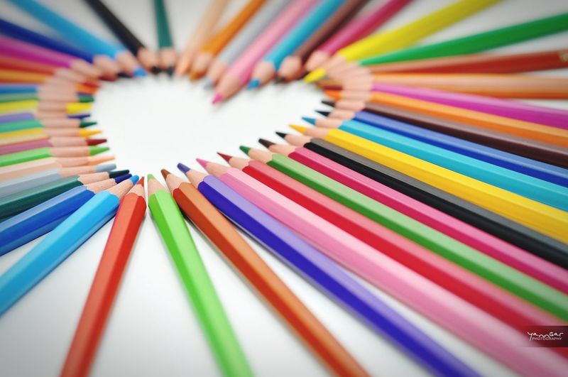 Close-up of colored pencils in heart shape on table