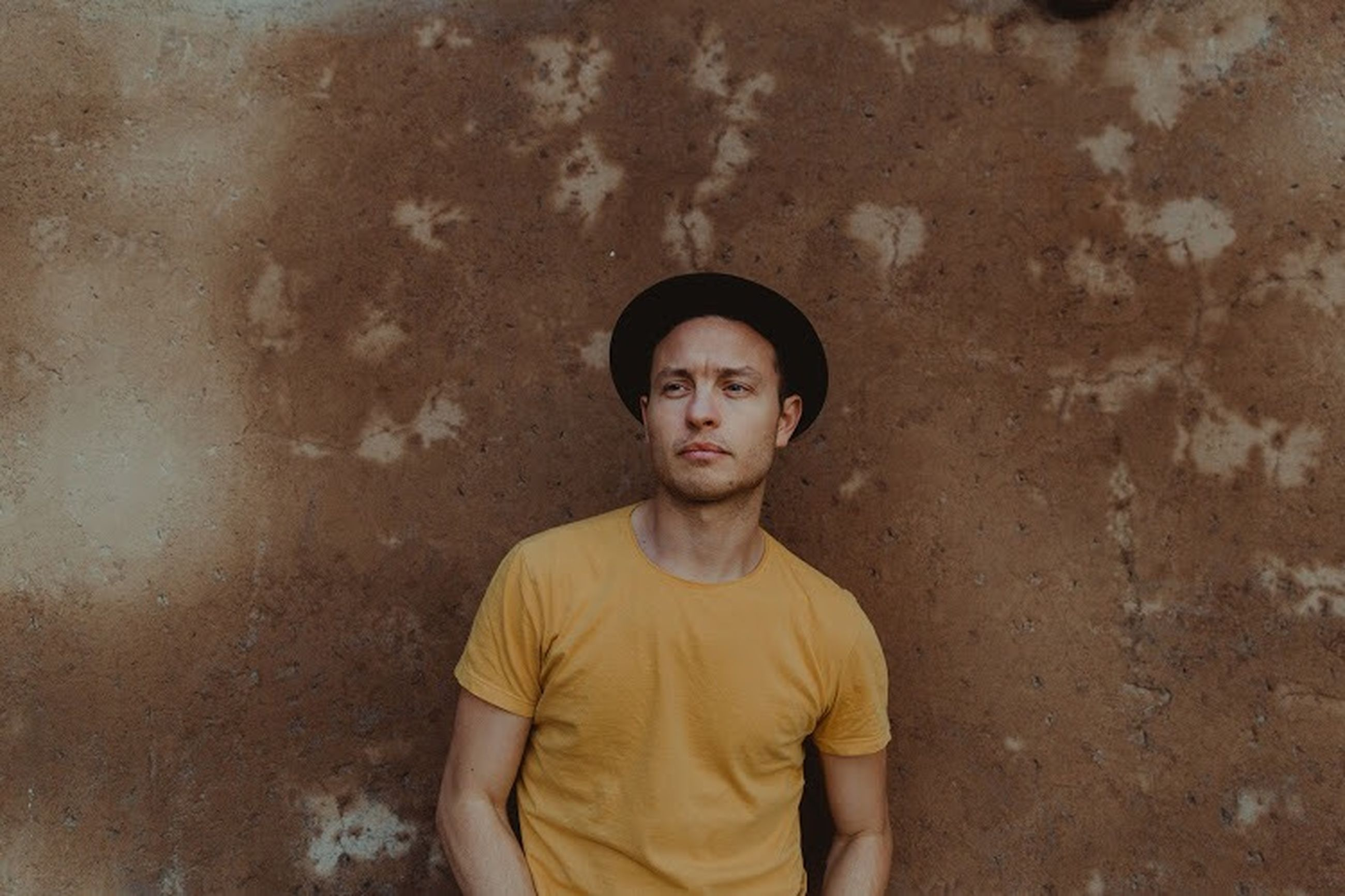 portrait, one person, looking at camera, casual clothing, young adult, standing, front view, wall - building feature, serious, lifestyles, young men, teenager, contemplation, t-shirt, yellow, day, child, leisure activity, adolescence, teenage boys