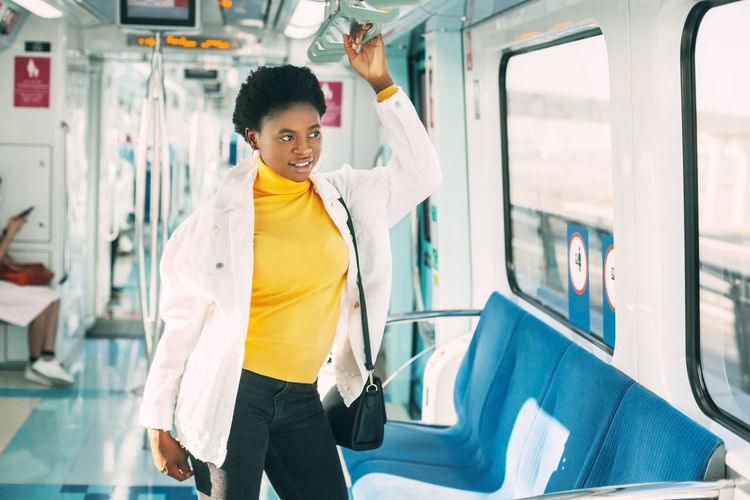 A smiling young african woman holds on to a handrail while standing on a subway