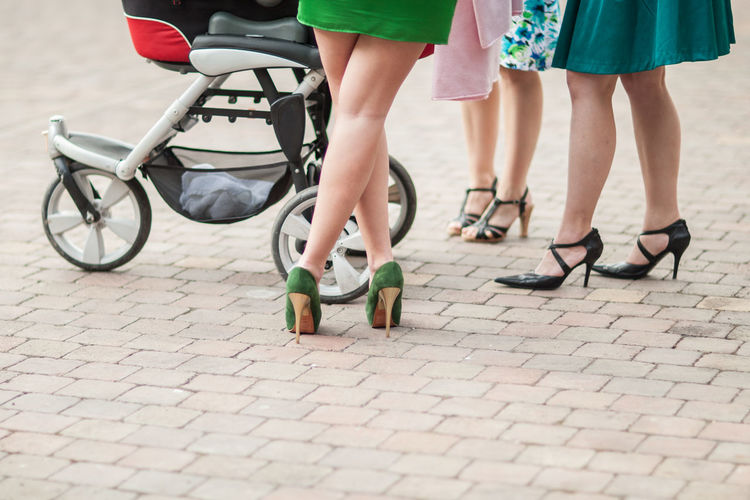 Low Section Of Women Wearing High Heels Standing By Baby Stroller On Footpath