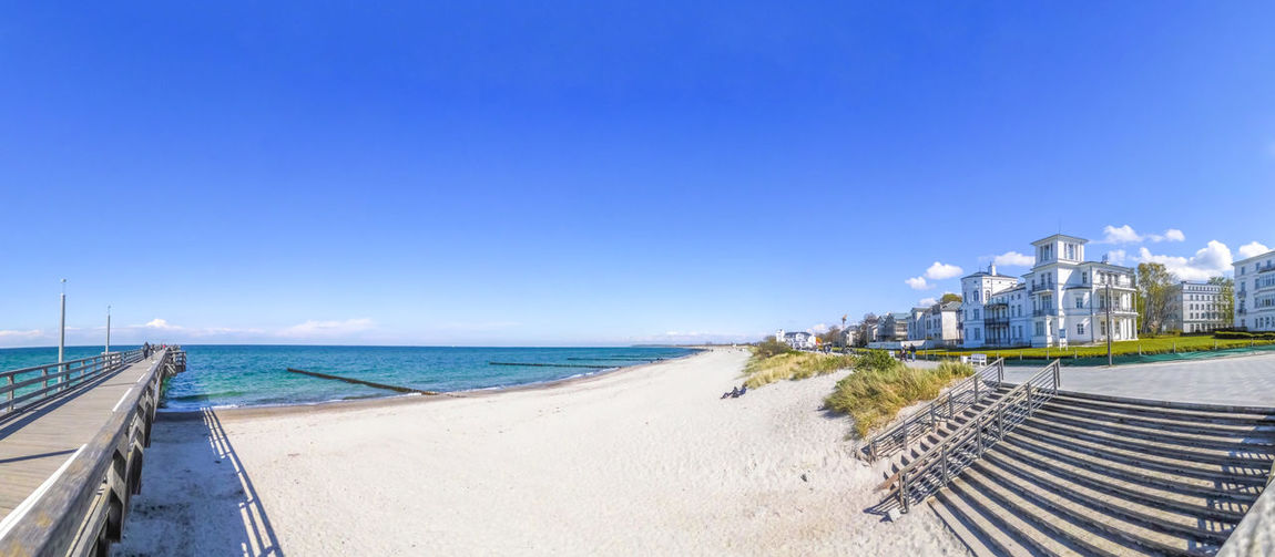 Scenic view of beach against clear blue sky on sunny day