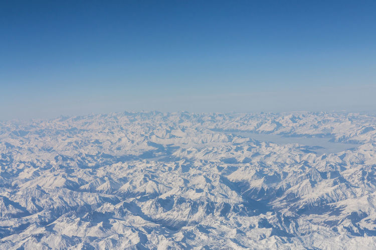 Aerial view of snowcapped landscape against clear blue sky