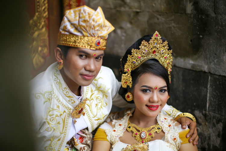 The bride and groom in traditional clothes are sitting