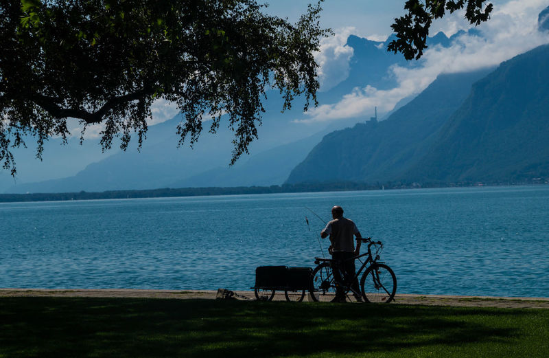 Rear view of man against calm lake