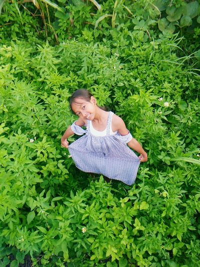 High Angle View Of Cute Girl Standing On Field Amidst Plants