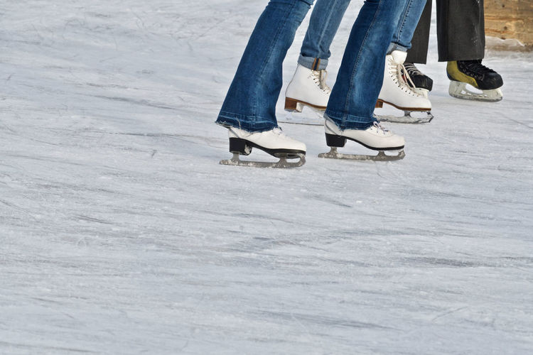 Low section of people ice-skating on ice rink during winter
