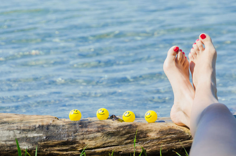 Female girl resting with her legs on a tree trunk at the waterfront with balloons with smiley faces on the wood Baloons Baloons🎈 EyeEmNewHere Lake Constance Sunbathing☀ Bodensee Female Legs Smiley Smiley Face Sun Sunbathing Waterfront Wooden Trunk Yellow