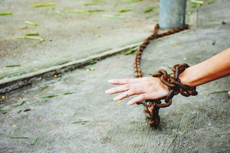 Cropped Hand Of Woman Locked In Rusty Metallic Chain