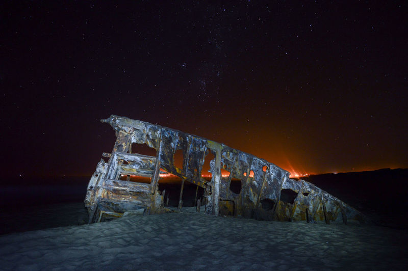 Shipwreck At Beach Against Sky During Night