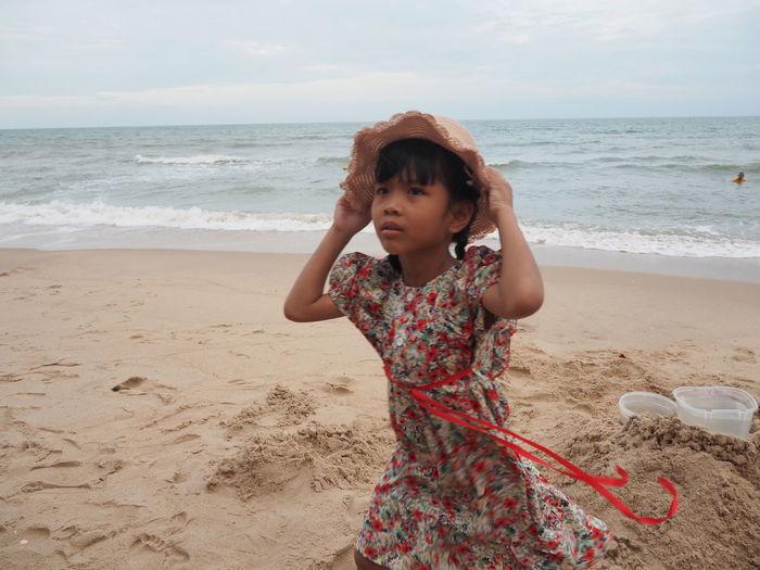 Happy girl on beach against sky