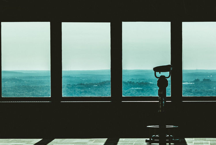 Silhouette against sky seen through window