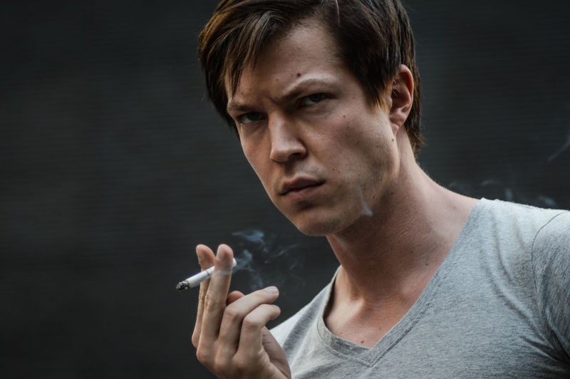 Addiction Adult Adults Only Bad Habit Cigarette  Close-up Danger Day Headshot Holding Indoors  Lifestyles Looking At Camera One Person People Portrait Real People RISK Smoke - Physical Structure Smoking - Activity Smoking Issues Social Issues Young Adult