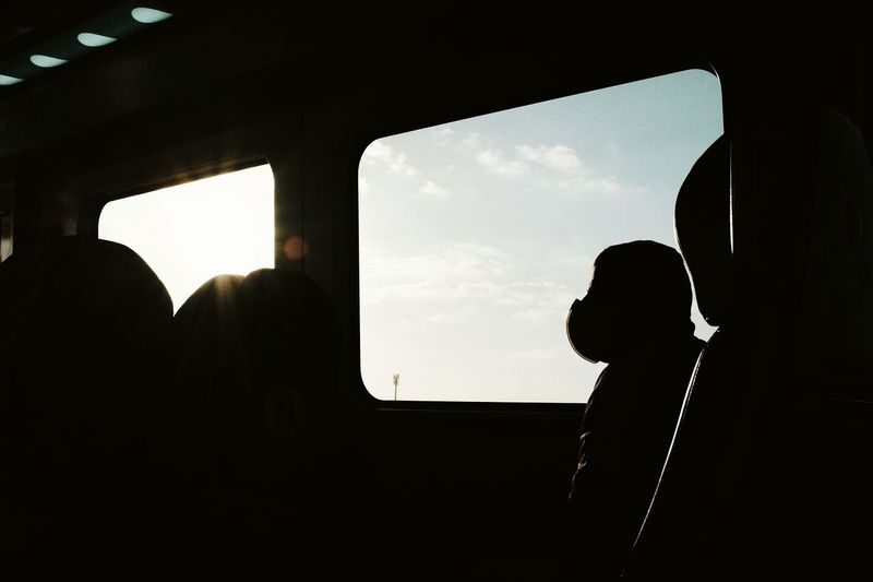 Silhouette man seen through airplane window