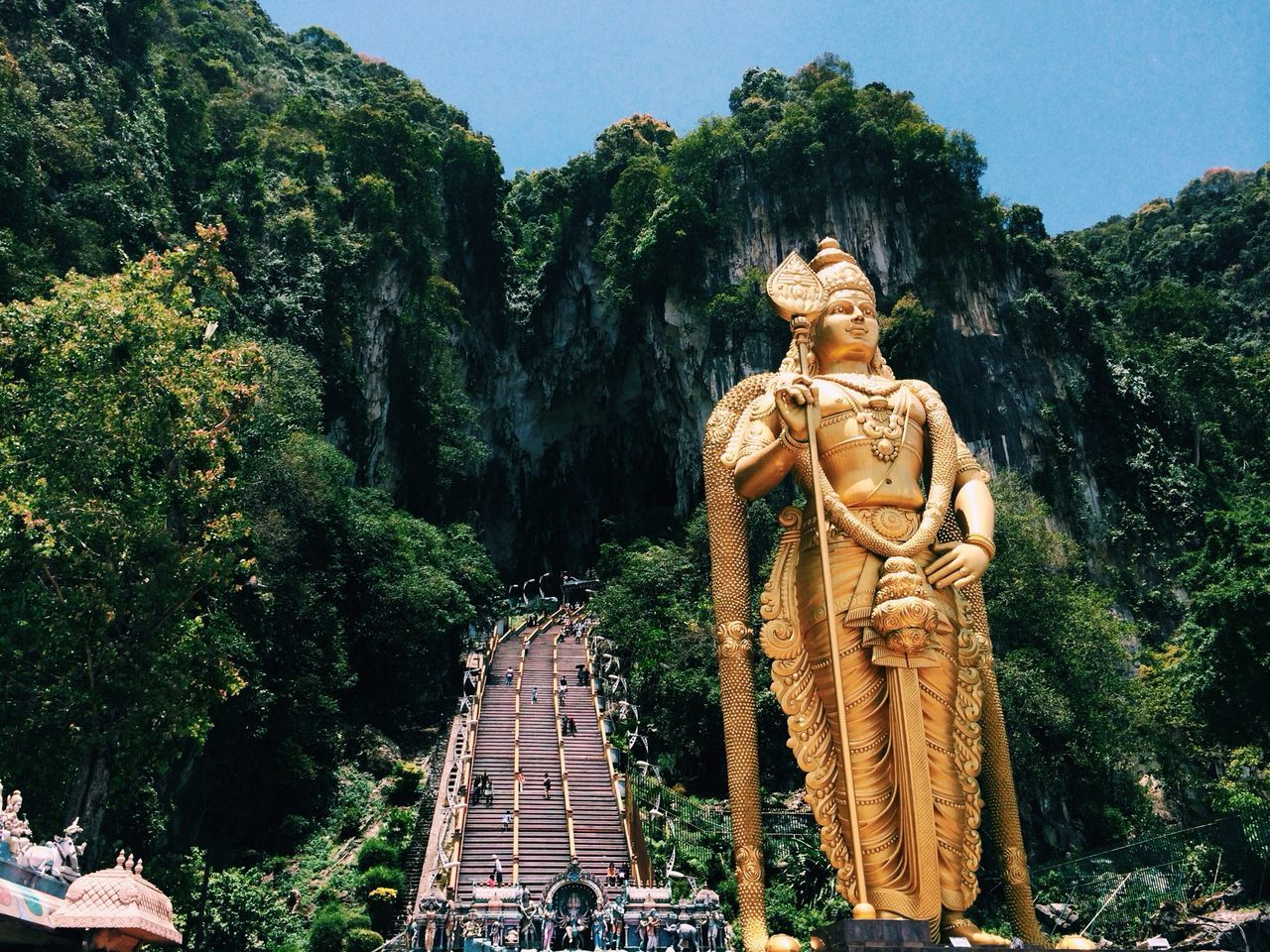 Low angle view of lord murugan statue at batu caves against clear sky