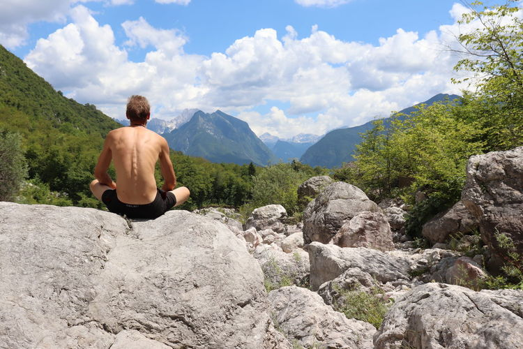 Rear view of shirtless man sitting on rock against mountains