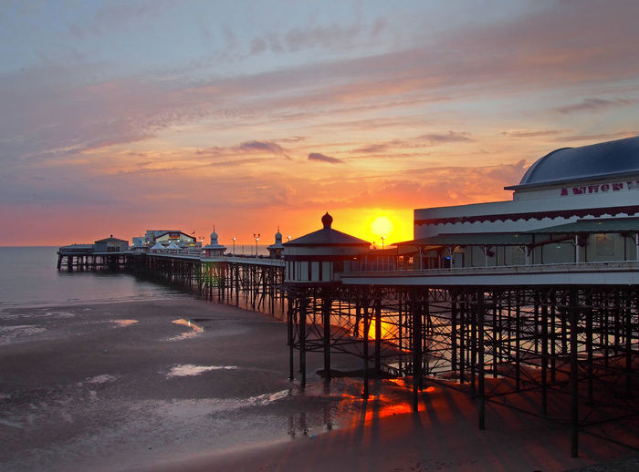 the sun setting over the historic north pier in blackpool with glowing light reflected on the beach and colourful twilight sky Blackpool Blackpool North Pier Britain Pier Twilight Beach Beauty In Nature Cloud - Sky Coast Dusk Idyllic Nature Orange Color Outdoors Pier Reflection Sea Seascape Shore Sky Summer Sunset Travel Destinations Twilight Sky Water