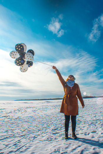 One Person Sky Winter Real People Leisure Activity Lifestyles Snow Full Length Nature Cloud - Sky Young Adult Warm Clothing Cold Temperature Happiness Mid-air Land Day Front View Outdoors Woman