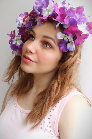 Portrait of beautiful woman with flower crown against wall