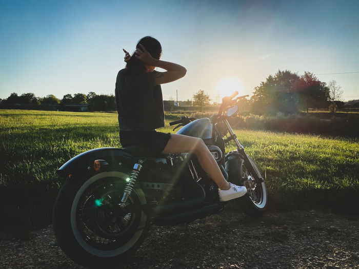 Woman sitting on motorcycle against sky during sunset