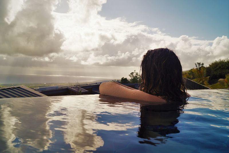 Rear view of woman relaxing in infinity pool against sky