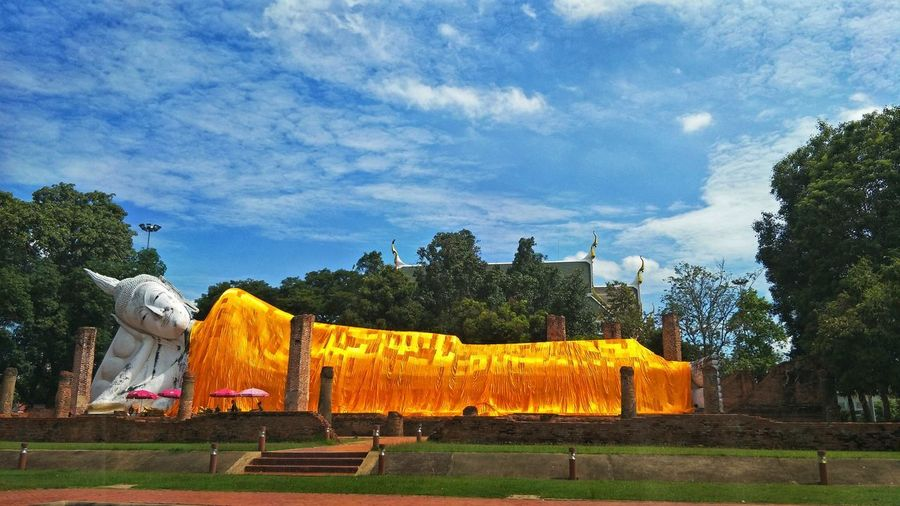 Yellow sculpture by trees against sky