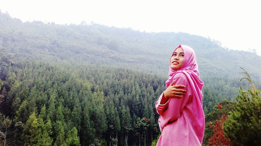 Young woman wearing hijab while standing against mountains