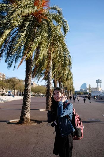 Portrait of smiling young woman standing on palm tree