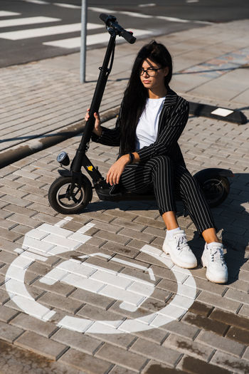 High angle view of woman with push scooter sitting on footpath