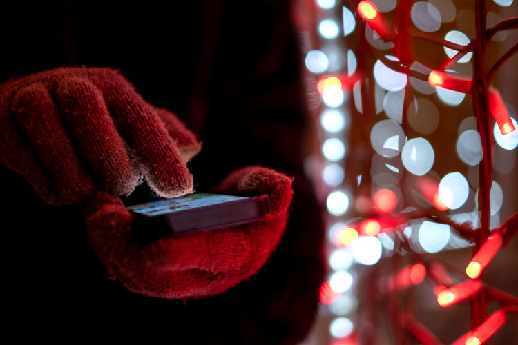 human hand using mobile at colorful bokeh background Illuminated Close-up Red Focus On Foreground Night Lighting Equipment Glow In The Dark Decoration Black Background Electricity  Art And Craft Clothing Technology Creativity Connection Using My Mobile Colorful Christmas Christmas Lights Using Technology Winter Wonderland Selective Focus Wool