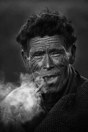Close-Up Portrait Of Senior Man Smoking Pipe