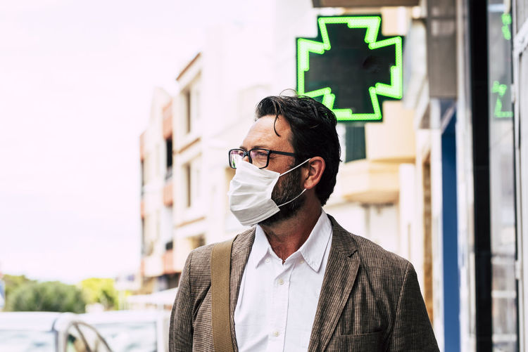 Mature man wearing face mask looking away against building