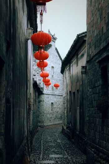 Red lanterns hanging on wall by old building