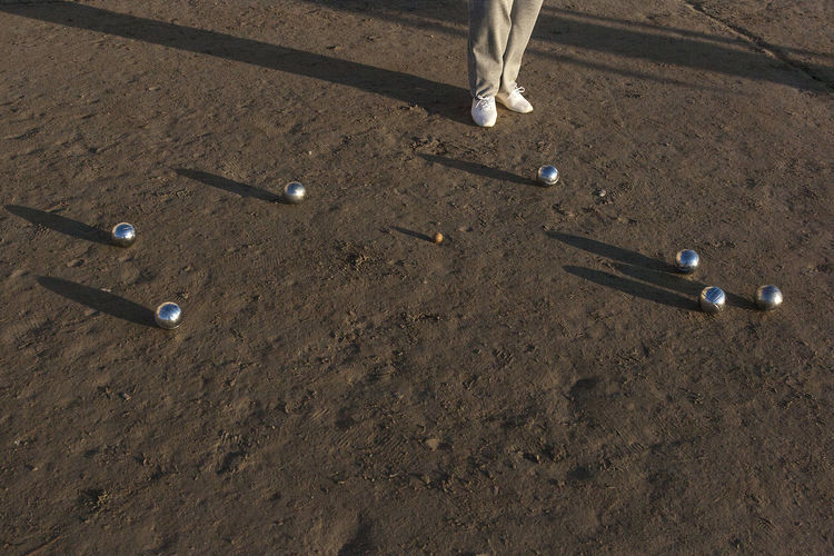 Low section of person standing by balls on mud