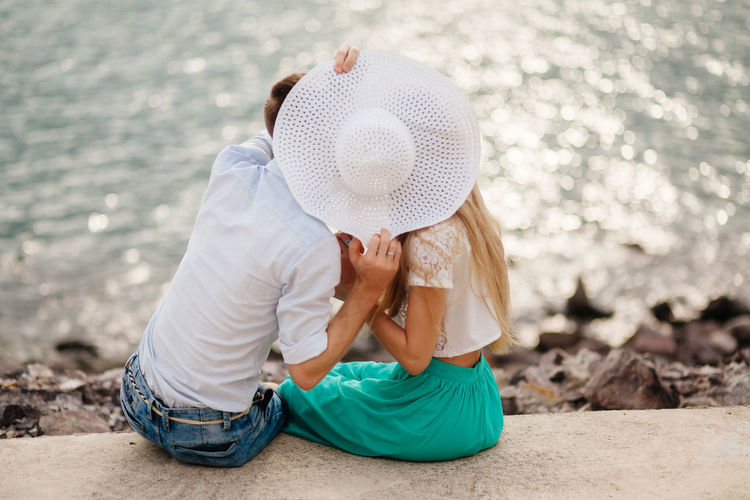 Couple With Hat Romancing On Retaining Wall By Sea