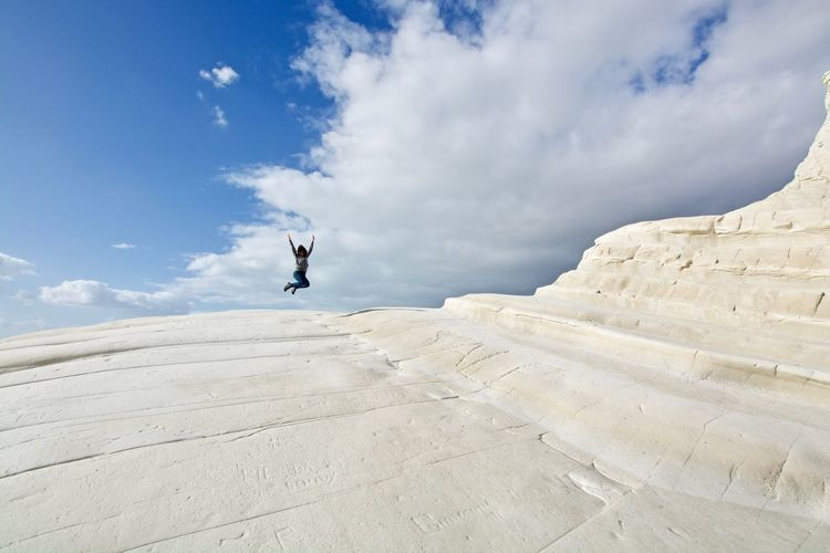Full length of man jumping in mid-air against sky