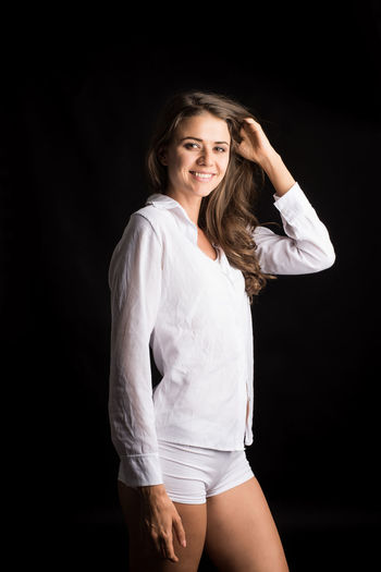 Looking At Camera Three Quarter Length Black Background Studio Shot One Person Young Adult Young Women Indoors  Smiling Portrait Front View Women Happiness Hairstyle Standing Lifestyles Beauty Beautiful Woman Casual Clothing Hair