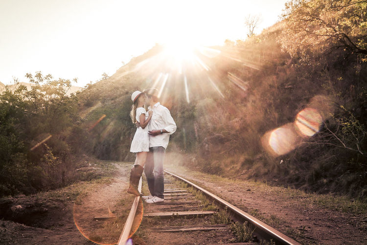 A COUPLE IN LOVE KISSING ON the railroad tracks in the evening of a spring afternoon Argentina Couple Kiss Love Lovers Pair Railroad Real People Spring Sunset