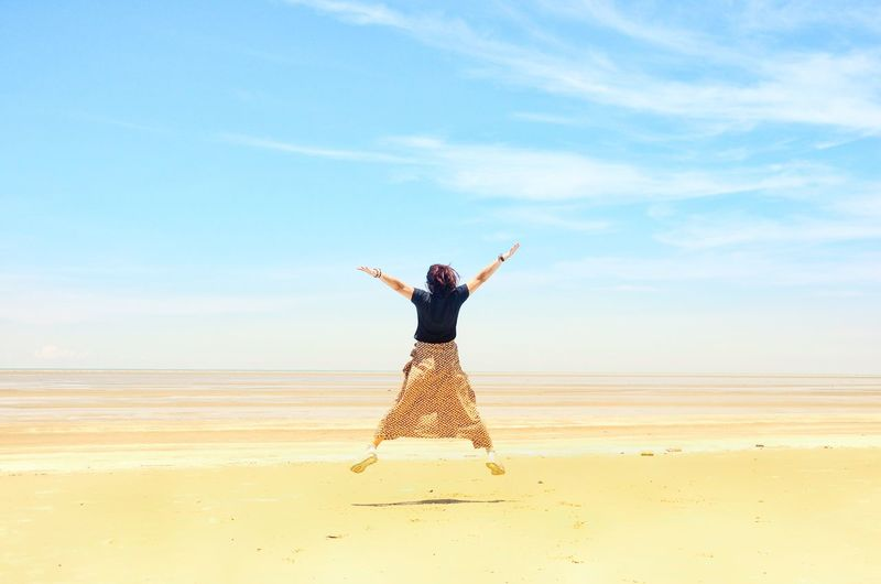 Rear view of woman jumping on sand at beach against sky
