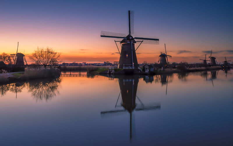 Remo SCarfo Sky Sunset Reflection Water Beauty In Nature Waterfront Tranquility Fuel And Power Generation Turbine Orange Color Scenics - Nature Tranquil Scene Environmental Conservation No People Wind Turbine Nature Lake Renewable Energy Wind Power Holland Kinderdijk Windmills Dutch