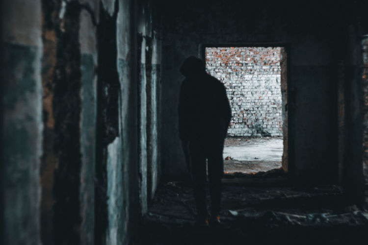 Rear view of silhouette man standing in abandoned building